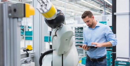 Industry 4.0 Engineer Using a Robot Arm